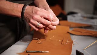 Craftsman sewing with a needle the strap of handmade leather notebook cover