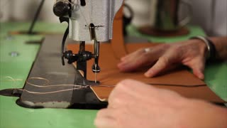 Craftsman stitching two leather pieces with sewing machine in his workshop. Slowly and carefully so stiches are the same.