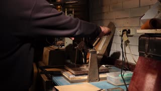 Craftsman taking leather piece from manual embossing press machine