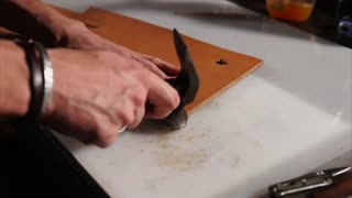 Craftsman using hammer to tap on the edges of leather product to join parts after glueing. Making handmade notebook