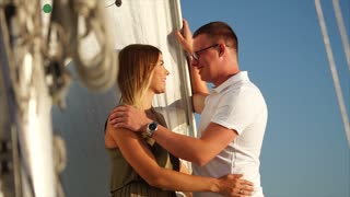 Cute young cople is spending romantic evening aboard the yacht together. Woman softly caresses face of her man.