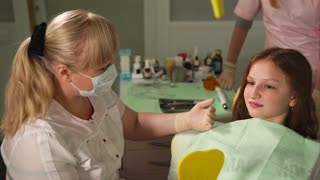 Dentist explain something to teenage girl patient. Work with child. Beautiful blonde female dentist. Conversation between dentist and child.