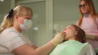 Dentist light tooth filling with ultraviolet. Tooth filling. Child patient. Dentist working with child.