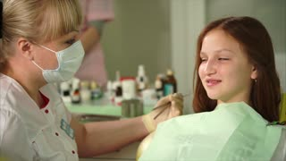 Dentist talking with young patient. Young girl attending dentist. Beautiful blonde female dentist. Conversation between dentist and child.