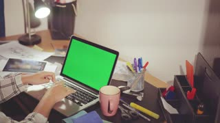Designer desktop with laptop chroma key on the screen, she choose good color.