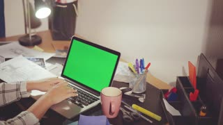 Designer in his office enters the information on laptop chroma key on the screen