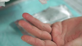 Doctor wipes with disinfectant a patient's finger before a blood test. Close up view of hand