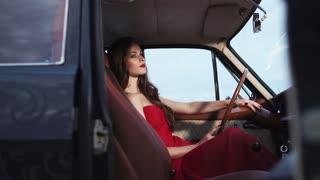 Elegant and swell-dressed woman is sitting behind the wheel of a retro car. Her dress and make up are beautiful.