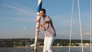 Emotional and charismatic man dances on a yacht that is in the sea, the person actively moves to the music and smiles, the water boat swims in the daytime