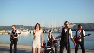 Energetic and cheerful musicians perform a melody in the daytime, men and women play drums, guitars, and sing a song in a microphone, soloists dance on the pier