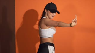 Energetic modern dance called hip-hop. Urban culture. Slow motion shot of young emotional woman in sportswear and cap performing hip-hop dance in the studio