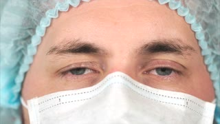 Extreme close-up of a man surgeon in medical hat and face mask looking to the camera