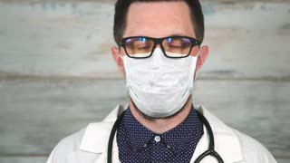 Face of male scientist or doctor in white protective mask. Concept of different professions. Close up view.