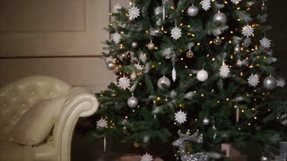 Fake spruce is decorated by white, silver and golden balls and snow-flakes and yellow lights in a dark room. Camera is moving from floor to top, Christmas and New Year time