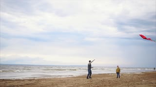 Family fun. Man with his son playing with kite. They running along the shore on a beach