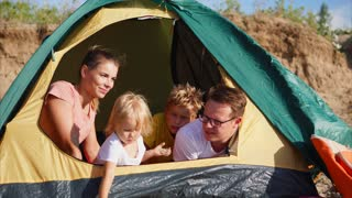 Family having great camping holidays. Happy mom, dad and two kids looking outside from the tent