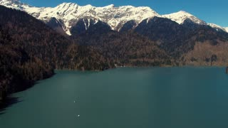 Fantastic view on the mountains, azure lake and forest in summertime. Snowy peaks of mountains. Majestic nature.