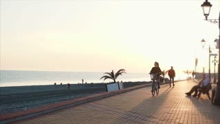 Fantastic young woman riding a bicycle on a beach during sunset, Beautiful sky in summer. Woman enjoying slow relaxing ride viewing sea.