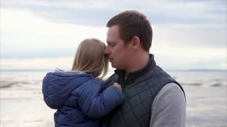 Father with daughter. Man holding and hugging little blonde girl. Windy cold weather. Ocean on background.