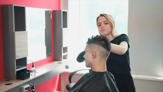 Female barber finishing haircut. She drying customers hair with hair dryer and hand