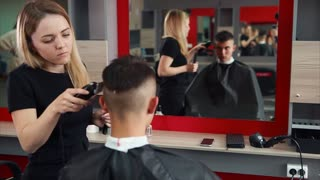 Female hairdresser at work. She trimming the hair by hair clipper. Male customer sitting on the chair