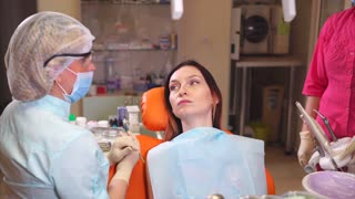 Female patient and dentist in dental cabinet. Female doctor making dental treatment and checkup
