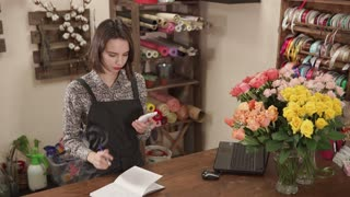 Female shop assistant is calculating using mobile phone, in a trading hall of flower shop. She is making notes in a log, notebook and vases with rose in a table