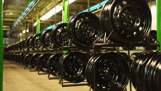 Finished pressed steel wheels are on shelves in production room in a factory. Modern full-cycle steel wheel production plant.