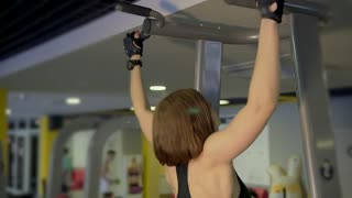 Fitness coach of the sports club does pull-ups on the simulator for strengthening the shoulder muscles. A woman does the exercises correctly, pulling up with a straight back.