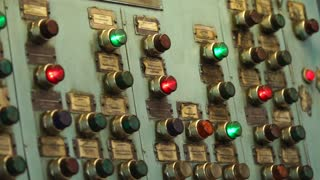 Flashing red and green lights inside keys of old central pane of production machine tool during operation. Automatical processes on industrial plant.