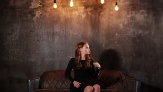 Flirting woman is sitting on a couch in studio with mysterious dark wall. She is curling her hair on a finger nervously