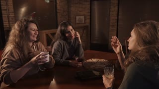 Four friends are talking in a pizzeria. Women and bearded man are sipping mixed drinks in dark hall of cozy restaurant in evening