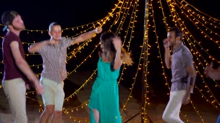 Friends having a good time together. They relaxing and dancing at night beach party