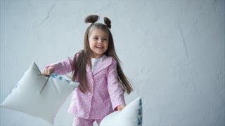 Funny little girl jumping on bed with pillows in her hands. Happy childhood.