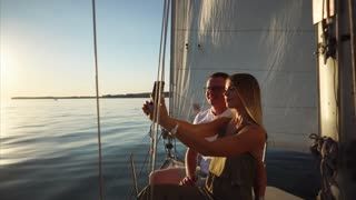 Girl and guy are taking self-portrait photo by phone on a yacht in evening. Woman is holding phone, they are smiling and posing on background of big sail.