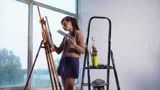 Girl artist is applying colors on a sheet, fixed on the easel. She is making detail and retreating for watching picture generally.