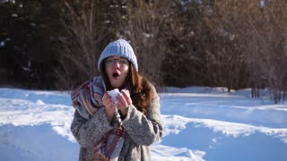 Girl in winter forest fun. Brunette blows snow from her hands.
