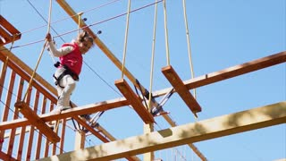 Girl overcoming obstacles and climbing hanging construction in adventure park. Outdoor active leisure for children