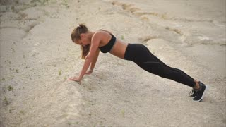 Girl working out to stay in a good shape. She doing leg lift exercise in front plank position. Taking sports outdoor