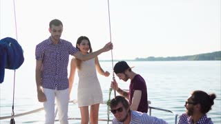 Group of friends having party during the cruise. They dancing on the yacht against bright sunlight