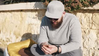 Grown man wearing grey sweater, jeans, cap and shandes sits on a bench outdoor under the sun. He is holding smartphone and chatting.