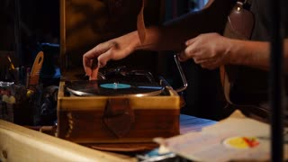 Guy puts on a music on retro vinyl recorder in a workshop. He is turning crank on a vinyl player and disk is spinning.