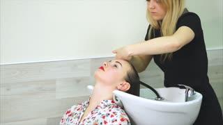 Hair salon. Woman customer getting hair wash with shampoo in beauty salon. Woman hairdresser at work