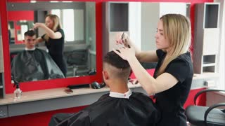 Hairdresser cuts hair for fashionable man who came to change his hair, a hair stylist cuts the unnecessary length of hair from the top to change the image