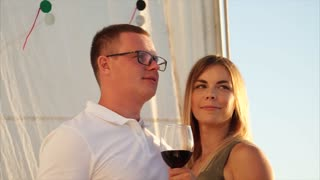Handsome man and beautiful woman are dinning on a luxury pleasure boat. Standing with glasses of red wine and enjoying of sunset on open sea