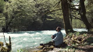 Handsome man in a jeans jacket is sitting at river's bank alone and relaxing. Spending day in the forest. Fast flowing river.