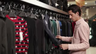 Handsome man is touching sweaters hanging on rack in store. He is taking one from hanger and applying to his body