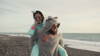 Handsome man with a beard is carrying on the back his charming girlfriend. They are wearing funny unicorn and wolf kigurumi costumes.