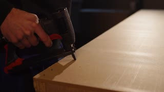 Handy man is using staple gun assembling piece of furniture in a workshop. He is stapling really fast.
