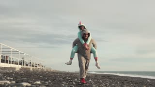Happy couple are having fun on the beach in the evening wearing kigurumi. Big man is carrying his girlfriend on his back.